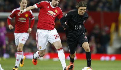 FILE - A Thursday, Feb. 25, 2016 file photo of Manchester United's Morgan Schneiderlin, center, and Midtjylland's Jakob Poulsen during the Europa League round of 32 second leg soccer match between Manchester United and FC Midtjylland in Manchester, England. Manchester United manager Jose Mourinho said Tuesday, Jan. 10, 2017 that the club is close to selling midfielder Morgan Schneiderlin to English Premier League rival Everton. The 27-year-old Schneiderlin has been told he can leave United after failing to establish himself in the team following his move from Southampton in July 2015. (AP Photo/Jon Super, File)