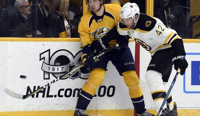 Nashville Predators left wing Filip Forsberg (9), of Sweden, passes the puck as he is defended by Boston Bruins right wing David Backes (42) during the first period of an NHL hockey game Thursday, Jan. 12, 2017, in Nashville, Tenn. (AP Photo/Mark Zaleski)