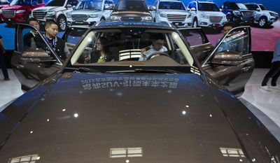 In this photo taken Monday, April 25, 2016, visitors to the Auto China 2016 examine the latest SUV from Chinese automaker Haval in Beijing, China. Industry figures released Jan 12, 2017, show China's auto market had a bumper year in 2016 as sales grew by 15 percent, with drivers rushing to buy cars before a tax break expired at the end of the year. (AP Photo/Ng Han Guan)