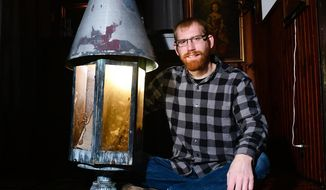 ADVANCE FOR USE SUNDAY, JAN. 15, 2017 AND THEREAFTER - In this Dec. 28,  2016 photo, David Powell poses with a gas lantern at his home in Cambridge, Ill. The lantern was originally inside the former Jumer's Castle Lodge in Bettendorf, Ill. Powell is decorating his home in the style of a castle lodge with features from Jumer's Castle Lodge. (Meg McLaughlin/The Dispatch via AP)