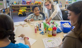 ADVANCE FOR USE SUNDAY, JAN. 15, 2017 AND THEREAFTER - In this Dec. 22,  2016 photo, teacher Lauren Halverson, center, works with Children's Hospital of Illinois patient Cortez Smith during an art class at the hospital in Peoria, Illinois. The room is packed with school supplies, books, computers and the desks of the three staff members who comprise the pediatric school. It serves as ground zero for the small staff and group of volunteers who help the thousands of school-age children who spend time in the hospital each year. (David Zalaznik/Journal Star via AP)