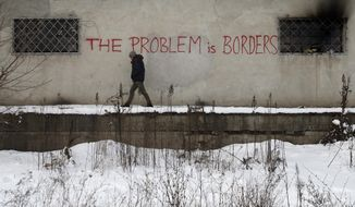 "A migrant passes by a graffiti reading ""The problem is borders"" featured on a wall of a crumbling warehouse that has served as a make-shift shelter for hundreds of men trying to reach Western Europe in Belgrade, Serbia, Thursday, Jan. 12, 2017. Migrants have been exposed to freezing temperatures and snow as extreme winter weather gripped Serbia and other parts of Europe last week. (AP Photo/Darko Vojinovic)"