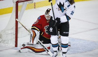 San Jose Sharks' Joe Thornton, right, screens Calgary Flames goalie Chad Johnson on a shot during the second period of an NHL hockey game Wednesday, Jan. 11, 2017, in Calgary, Alberta. (Jeff McIntosh/The Canadian Press via AP)