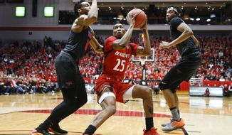 Cincinnati's Kevin Johnson (25) looks to pass against SMU's Jarrey Foster, left, and Ben Moore, right, during the first half of an NCAA college basketball game, Thursday, Jan. 12, 2017, in Cincinnati. (AP Photo/John Minchillo)