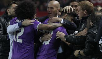 Real Madrid's coach Zidane, celebrates with Real Madrid's players after scored Marco Asensio during a Spain's King's Cup soccer match between Real Madrid and Sevilla at the Ramon Sanchez Pizjuan stadium, in Seville, Spain on Thursday, Jan. 12, 2017. (AP Photo/Angel Fernandez)