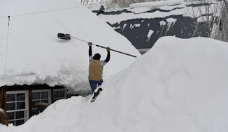 In this Tuesday, Jan. 10, 2017, Rob Quint works to pull snow off of the house of his roof in Crested Butte, Colo. About 93 inches has fallen in the area in 8 days and more is expected over the week. Quint says in the 35 years that he has lived in Crested Butte he has never seen this amount of snow. (Helen H. Richardson/The Denver Post via AP)