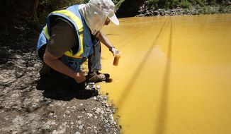 FILE - In this Aug. 6, 2015 file photo, Dan Bender, with the La Plata County Sheriff's Office, takes a water sample from the Animas River near Durango, Colo. after the accidental release of an estimated 3 million gallons of waste from the Gold King Mine by a crew led by the U.S. Environmental Protection Agency. The EPA said Friday, Jan. 13, 2017 that it wont pay claims totaling more than $1.2 billion for economic damages from the spill, saying the law prohibits it.  (Jerry McBride /The Durango Herald via AP, File)