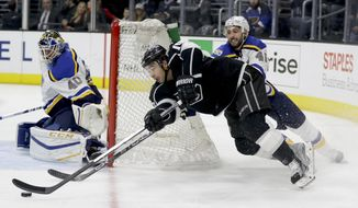 St. Louis Blues goalie Carter Hutton, left, blocks a shot by Los Angeles Kings right wing Devin Setoguchi as defenseman Robert Bortuzzo watches during the second period of an NHL hockey game in Los Angeles, Thursday, Jan. 12, 2017. (AP Photo/Chris Carlson)