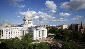 FILE - In this June 16, 2011, file photo, clouds roll over the Wisconsin state Capitol in Madison. A bipartisan commission is planning a months-long celebration for the building's 100th anniversary with a kick-off event beginning Jan. 31, 2017. (Michael P. King/Wisconsin State Journal via AP, File) /Wisconsin State Journal via AP)