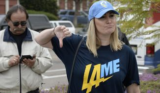 Bre Priest gives the thumbs down while wearing a t-shirt mocking the team at San Diego Chargers headquarters after the team announced that it will move to Los Angeles, Thursday Jan. 12, 2017, in San Diego. (AP Photo/Denis Poroy)