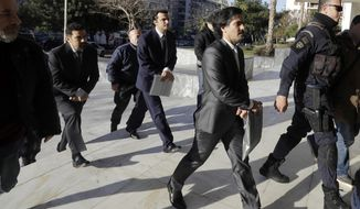 Three Turkish military officers in suits wearing handcuffs, escorted by Greek police officers, arrive at the Supreme Court in Athens Friday, Jan. 13, 2017. A prosecutor at Greece's highest court recommended Tuesday and Wednesday the court reject an extradition request for four other Turkish servicemen, who fled to Greece after a failed July military coup in their country. (AP Photo/Thanassis Stavrakis)