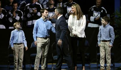 Former Tampa Bay Lightning right winger Martin St. Louis greets his family, from left, sons Lucas and Ryan, his wife, Heather, and son Mason during a jersey retirement ceremony before an NHL hockey game between the Lightning and the Columbus Blue Jackets on Friday, Jan. 13, 2017, in Tampa, Fla. (AP Photo/Chris O'Meara)