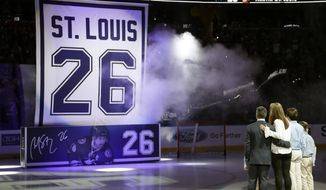 Former Tampa Bay Lightning right winger Martin St. Louis stands with his family as a banner bearing his number is raised during jersey retirement ceremony before an NHL hockey game between the Lightning and the Columbus Blue Jackets on Friday, Jan. 13, 2017, in Tampa, Fla. (AP Photo/Chris O'Meara)