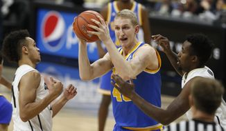 UCLA center Thomas Welsh, center, looks to shoot as Colorado guard Derrick White, left, and forward Wesley Gordon defend during the first half of an NCAA college basketball game late Thursday, Jan. 12, 2017, in Boulder, Colo. (AP Photo/David Zalubowski)