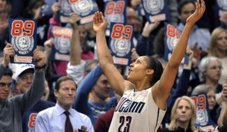 FILE - In this Dec. 21, 2010, file photo, Connecticut forward Maya Moore celebrates near the end of the team's NCAA college basketball game against Florida State in Hartford, Conn. Connecticut won 93-62 to to set an NCAA record for consecutive wins, at 89. Moore has been watching UConn intently, cheering for every win. The former Huskies great, who was instrumental in the previous 90-game winning streak, hopes the current team can keep their current run going and shatter the mark her group set a few years ago. (AP Photo/Jessica Hill, File)