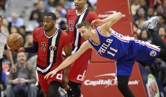 Washington Wizards guard John Wall (2) handles the ball against Philadelphia 76ers guard Nik Stauskas (11) during the second half of an NBA basketball game, Saturday, Jan. 14, 2017, in Washington. Wizards forward Otto Porter Jr. (22) looks on. (AP Photo/Nick Wass)