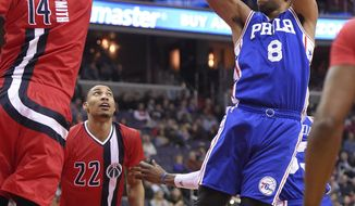 Philadelphia 76ers center Jahlil Okafor (8) shoots against Washington Wizards forward Jason Smith (14) and forward Otto Porter Jr. (22) during the first half of an NBA basketball game, Saturday, Jan. 14, 2017, in Washington. (AP Photo/Nick Wass)