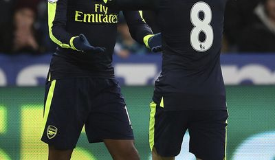 Arsenal's Alex Iwobi, left, celebrates his side's second goal of the game after his shot was deflected resulting in a own goal for Swansea City's Jack Cork during the English Premier League soccer match between Swansea City and Arsenal at the Liberty Stadium, Swansea, Wales, Saturday, Jan. 14, 2017.(Nick Potts/PA via AP)