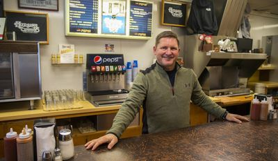 ADVANCE FOR SATURDAY, JAN. 14, 2017 - In this Friday, Jan. 6, 2017 photo, Steve Hudson, co-owner of Hudson's Hamburgers with his brother, Todd, poses inside Hudson's in Coeur d'Alene, Idaho. For years, Hudson's Hamburgers has provided a good social atmosphere for locals and tourists to mingle as their food is prepared in front of them. (Loren Benoit/Coeur D'Alene Press via AP)
