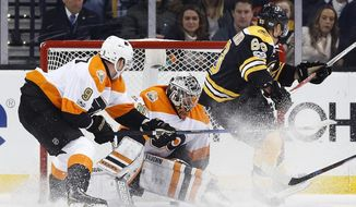 Boston Bruins' Brad Marchand (63) scores on Philadelphia Flyers' Michal Neuvirth (30), of the Czech Republic, as Ivan Provorov (9), of Russia, defends during the first period of an NHL hockey game in Boston, Saturday, Jan. 14, 2017. (AP Photo/Michael Dwyer)