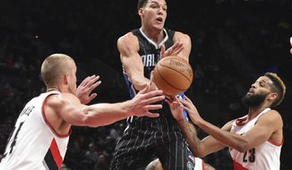 Orlando Magic forward Aaron Gordon passes the ball as Portland Trail Blazers center Mason Plumlee and guard Allen Crabbe defend during the first half of an NBA basketball game in Portland, Ore., Friday, Jan. 13, 2017. (AP Photo/Steve Dykes)