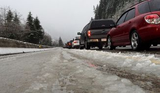 FILE - In this Dec. 10, 2015 file photo, vehicles along eastbound Interstate 90 heading up Snoqualmie Pass are stopped in snow and slush during a road closure in Washington state. The recent deaths of two Washington State University students driving back to campus in Pullman, Wash., after winter break have revived concerns about the safety of roadways leading to the rural college town. (AP Photo/Ted S. Warren, file)