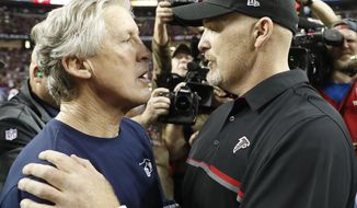 Seattle Seahawks head coach Pete Carroll, left, speaks with Atlanta Falcons head coach Dan Quinn after an NFL football divisional football game, Saturday, Jan. 14, 2017, in Atlanta. The Falcons won 36-20. (AP Photo/John Bazemore)