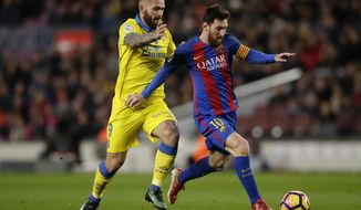 FC Barcelona's Lionel Messi, left, duels for the against Las Palmas' Mauricio Lemos during the Spanish La Liga soccer match between FC Barcelona and Las Palmas at the Camp Nou in Barcelona, Spain, Saturday, Jan. 14, 2017. (AP Photo/Manu Fernandez)