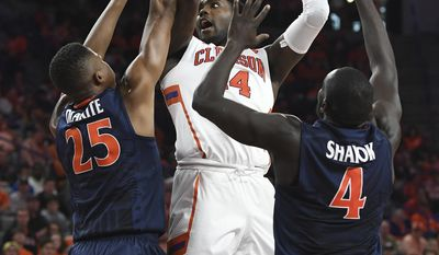Clemson forward Elijah Thomas (14) shoots between Virginia forward Mamadi Diakite (25), left, and guard Marial Shayok (4) during the second half of an NCAA college basketball game, Saturday, Jan. 14, 2017 at Littlejohn Coliseum in Clemson, S.C. (Bart Boatwright/The Greenville News via AP)