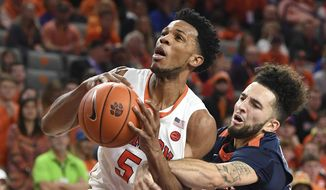 Virginia guard London Perrantes, right, tries to knock the ball from Clemson forward Jaron Blossomgame (5) during the second half of an NCAA college basketball game, Saturday, Jan. 14, 2017 at Littlejohn Coliseum in Clemson, S.C. (Bart Boatwright/The Greenville News via AP)