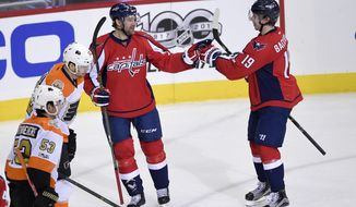 Washington Capitals right wing Justin Williams (14) celebrates his goal with center Nicklas Backstrom (19), of Sweden, during the third period of an NHL hockey game as Philadelphia Flyers defenseman Shayne Gostisbehere (53) and left wing Michael Raffl (12), of Austria, skate b y, Sunday, Jan. 15, 2017, in Washington. (AP Photo/Nick Wass)