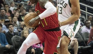 Atlanta Hawks guard Dennis Schroder, of Germany, drives to the basket as Milwaukee Bucks guard Malcolm Brogdon (13) defends during the first half of an NBA basketball game, Sunday, Jan. 15, 2017, in Atlanta. (AP Photo/John Amis)