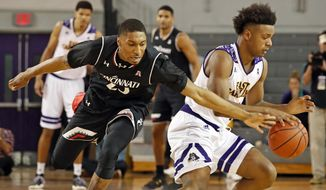 Cincinnati's Kevin Johnson (25) tries to steal the ball from East Carolina's Elijah Hughes (4) during the first half of an NCAA college basketball game in Greenville, N.C., Sunday, Jan. 15, 2017. (AP Photo/Karl B DeBlaker)