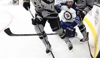 Los Angeles Kings center Anze Kopitar, left, of Slovenia, moves the puck as Winnipeg Jets right wing Drew Stafford, center, reaches in and defenseman Derek Forbort skates behind during the first period of an NHL hockey game, Saturday, Jan. 14, 2017, in Los Angeles. (AP Photo/Mark J. Terrill)