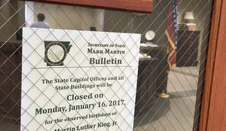 This Friday, Jan. 13, 2017, photo shows a sign on the door of a state treasurer's office in Little Rock, Ark., noting the joint holiday Jan. 16 observing the birthdays of slain civil rights leader Martin Luther King Jr. and Confederate Gen. Robert E. Lee. Gov. Asa Hutchinson is reviving an effort to remove Lee from the holiday. But he faces resistance from opponents who complain the move belittles the state's Confederate heritage and from black lawmakers worried about a plan to set aside another day to honor Lee. (AP Photo/Kelly Kissel)