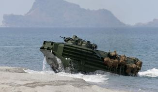 In this April 21, 2015, file photo, a U.S. Navy's amphibious assault vehicle with Philippine and U.S. troops on board storms the beach at a combined assault exercise at a beach facing one of the contested islands in the South China Sea known as the Scarborough Shoal in the West Philippine Sea at the Naval Education and Training Command at San Antonio township. (AP Photo/Bullit Marquez, File)