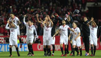 Sevilla's players celebrate at the end of the La Liga soccer match between Real Madrid and Sevilla at the Ramon Sanchez Pizjuan stadium, in Seville, Spain on Sunday, Jan. 15, 2017. Sevilla won 2-1.(AP Photo/Angel Fernandez)