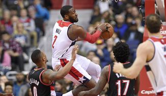 Washington Wizards guard John Wall (2) moves under the basket against Portland Trail Blazers guard Damian Lillard (0) and forward Ed Davis (17) during the first half of an NBA basketball game, Monday, Jan. 16, 2017, in Washington. (AP Photo/Nick Wass)