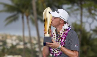 Justin Thomas kisses the trophy after winning the Sony Open golf tournament Sunday, Jan. 15, 2017, in Honolulu. Challenged only by the record book, Thomas won the Sony Open on Sunday with the lowest 72-hole score in PGA Tour history. (AP Photo/Marco Garcia)