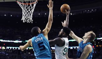 Boston Celtics forward Amir Johnson, center, tries to pass while surrounded by Charlotte Hornets guard Nicolas Batum (5) and center Cody Zeller, right, during the first quarter of an NBA basketball game in Boston, Monday, Jan. 16, 2017. (AP Photo/Charles Krupa)