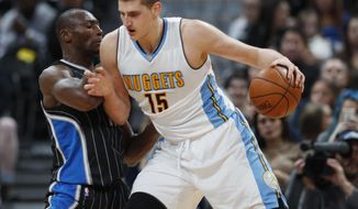 Denver Nuggets forward Nikola Jokic, right, of Serbia, works the ball inside for a shot as Orlando Magic center Bismack Biyombo, of the Congo, defends in the first half of an NBA basketball game Monday, Jan. 16, 2017, in Denver. (AP Photo/David Zalubowski)