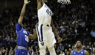 Villanova's Darryl Reynolds (45) goes up for a dunk against Seton Hall's Madison Jones (30) as Myles Powell (13) looks on during the first half of an NCAA college basketball game, Monday, Jan. 16, 2017, in Villanova, Pa. (AP Photo/Matt Slocum)