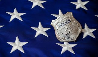 An Alexandria (Va.) Police Department badge is depicted here resting on a U.S. flag in a photo by Sgt. Jim Craige of the APD. (Photo: APD/Facebook) [https://www.facebook.com/AlexandriaVAPD/photos/a.187216998056705.34897.187216751390063/703231776455222/?type=1&theater]