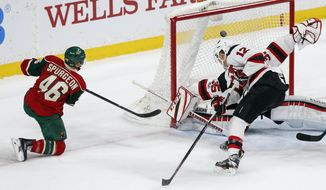 Minnesota Wild's Jared Spurgeon, left, scores a power-play goal against New Jersey Devils goalie Cory Schneider during the first period of an NHL hockey game Tuesday, Jan. 17, 2017, in St. Paul, Minn. (AP Photo/Jim Mone)