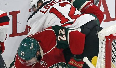 Minnesota Wild's Nino Niederreiter, left, of Switzerland, and New Jersey Devils' Ben Lovejoy collide behind the net during the first period of an NHL hockey game Tuesday, Jan. 17, 2017, in St. Paul, Minn. (AP Photo/Jim Mone)