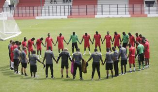 Togo's soccer team and team officials form a circle during their training session in Stade de Bitam, Gabon, Tuesday, Jan. 17, 2017, ahead of their African Cup of Nations Group C soccer match against Morocco. (AP Photo/Sunday Alamba)