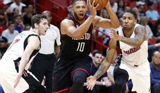 Houston Rockets guard Eric Gordon (10) drives past Miami Heat guard Goran Dragic, left, and guard Rodney McGruder during the first half of an NBA basketball game, Tuesday, Jan. 17, 2017, in Miami. (AP Photo/Wilfredo Lee)