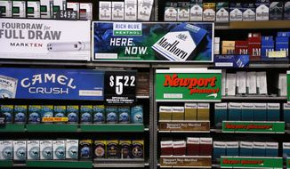 FILE - In this Friday, July 17, 2015 file photo, Camel and Newport cigarettes, both Reynolds American brands, are on display at a Smoker Friendly shop in Pittsburgh. British American Tobacco Plc has agreed to fully take over Reynolds American Inc. on terms that are improved from an initial bid made last year. (AP Photo/Gene J. Puskar, file)