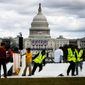 Workers place plastic flooring on the grass of the National Mall in Washington on Wednesday as preparations continue for Friday's presidential inauguration. Republicans say all seats will be filled. (Associated Press)