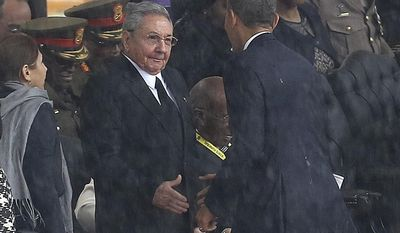 FILE - In this Tuesday Dec. 10, 2013 file photo, U.S. President Barack Obama shakes hands with Cuban President Raul Castro at the FNB Stadium in Soweto, South Africa, in the rain for a memorial service for former South African President Nelson Mandela. Africa was electrified by the rise of Barack Obama, the first U.S. president of African descent, who took aim at the twin scourges of corruption and dictatorship and sent thousands of troops to fight one of the most terrifying disease outbreaks in decades. (AP Photo, File) SOUTH AFRICA OUT